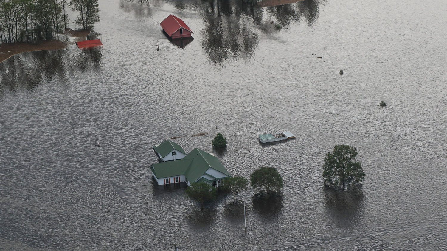 aerial view of a farmhouse, vehicles and outbuildings during a flood. all of the structures are submerged, leaving only roofs exposed